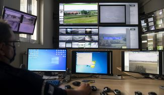 A police officer works inside the operation center at the village of Nea Vyssa near the Greek-Turkish border, in Greece, Friday, May 21, 2021. An automated hi-tech surveillance network being built on the Greek-Turkish border aiming at detecting migrants early and deterring them from crossing, with river and land patrols using searchlights and long-range acoustic devices. (AP Photo/Giannis Papanikos)