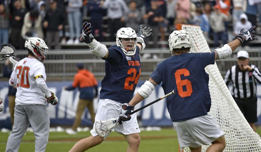 Virginia attack Payton Cormmier (24), center, celebrates a goal against Maryland with Virginia midfielder Dox Aitken (6) during the NCAA Division 1 men's lacrosse championship at Rentschler Field in East Hartford, Conn., Monday, May 31, 2021. (Brad Horrigan/Hartford Courant via AP)