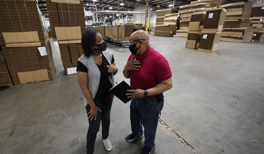 """Charita McCarrol, human resources manager at Great Southern Industries, a packaging company in Jackson, Miss., left, confers with second shift production manager James Chapman, Friday, May 28, 2021. McCarrol said she has seen people abusing the $300-a-week federal supplement for people who lost their jobs during the COVID-19 pandemic, as well as other programs that offered extended support for the unemployed. """"You can't get people to come to work,"""" McCarrol said. """"It has been an absolute nightmare in the world of staffing agencies."""" (AP Photo/Rogelio V. Solis)"""