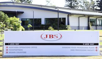 In this May 12, 2020, photo, the company logo sign sits at the entrance to the JBS Australia's Dinmore meatworks facility, west of Brisbane. Thousands of Australian meat workers had no work for a second day on Tuesday, June 1, 2021, after a cyberattack crippled the worlds largest meat processing company. A government minister said it might be days before production resumes. (Dan Peled/AAP Image via AP)