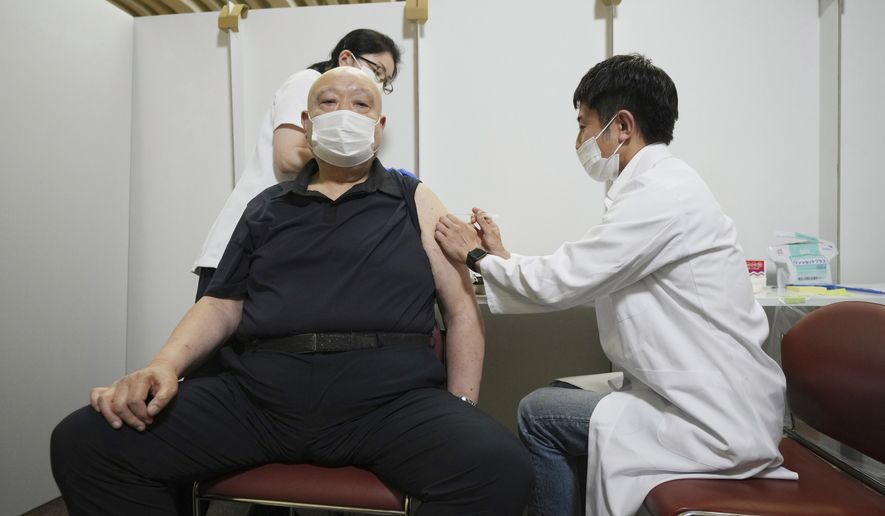 In this May 24, 2021, file photo, former sumo stable master Chiganoura, left, receives his first dose of Pfizer's COVID-19 vaccine at the Ryogoku Kokugikan sporting arena. The arena, mainly used for sumo wrestling tournaments, is being used as a temporary inoculation venue for residents over 65 years old in Tokyo. Japan, seriously behind in coronavirus vaccination efforts, is scrambling to boost daily shots as the start of the Olympics in July closes in. (AP Photo/Eugene Hoshiko, File)  **FILE**