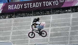 In this May 17, 2021, file photo, a local athlete competes during the Tokyo 2020 Olympic Game Cycling BMX Freestyle test event at Olympic BMX Course of Ariake Urban Sports Park in Tokyo. IOC officials say the Tokyo Olympics will open on July 23 and almost nothing now can stop the games from going forward. (AP Photo/Eugene Hoshiko, File) **FILE**