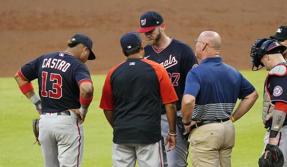 Washington Nationals starting pitcher Stephen Strasburg, center, talks with manager Dave Martinez and a member of the team's medical staff before exiting a baseball game in then second inning against Atlanta Braves Tuesday, June 1, 2021, in Atlanta. (AP Photo/John Bazemore) **FILE**