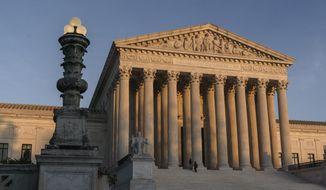 In this Nov. 6, 2020, file photo, The Supreme Court is seen as sundown in Washington. (AP Photo/J. Scott Applewhite) ** FILE **