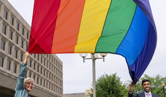 In this file photo, Energy Secretary Jennifer Granholm and Department of Energy Chief of Staff Tarak Shah, right, help raise the Progress Pride Flag outside the Department of Energy in Washington, Wednesday, June 2, 2021. The Department of Defense, meanwhile, is also honoring LGBT Pride month, but its existing ban on service members displaying Pride flags will remain in place, Pentagon spokesman John Kirby told reporters recently. (AP Photo/Andrew Harnik)  **FILE**