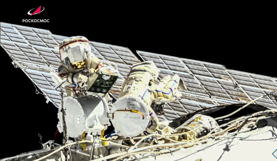 In this image taken from Roscosmos video, Russian cosmonauts Oleg Novitsky, left, and Pyotr Dubrov, members of the crew to the International Space Station (ISS), perform their first spacewalk on Wednesday, June 2, 2021, to replace old batteries outside the International Space Station. (Roscosmos via AP)
