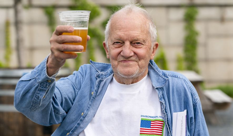 In this May 6, 2021, photo, George Ripley, 72, of Washington, holds up his free beer after receiving the J&J COVID-19 vaccine shot, at The REACH at the Kennedy Center in Washington. Free beer is the latest White House-backed incentive for Americans to get vaccinated for COVID-19. President Joe Biden announced a month of action on Wednesday to get more shots into arms before the July 4 holiday. (AP Photo/Jacquelyn Martin) ** FILE **