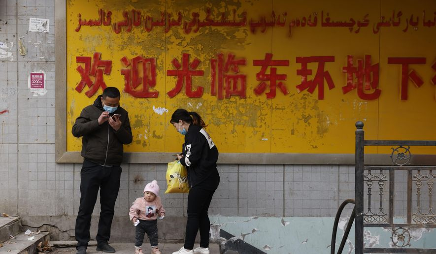 A family stands at the entrance to an underground retail street in Aksu in western China's Xinjiang Uyghur Autonomous Region on March 18, 2021. The U.S. State Department on July 13 released a report documenting human rights abuses targeting the Uyghurs. (AP Photo/Ng Han Guan)