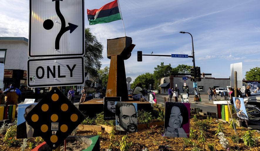 A traffic sign signals directions around the monument at George Floyd Square, Thursday, June 3, 2021, in Minneapolis. Crews are removing concrete barriers as well as artwork, flowers and other memorial items from a Minneapolis intersection that has become a sprawling memorial to George Floyd. (Carlos Gonzalez/Star Tribune via AP)