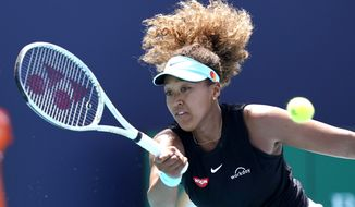In this March 31, 2021 file photo, Naomi Osaka, of Japan, returns to Maria Sakkari, of Greece, during the quarterfinals of the Miami Open tennis tournament in Miami Gardens, Fla.  Sponsors of Osaka are sticking by the her after she withdrew from the French Open citing mental health issues relating to the press conferences required for players. Osaka, a four-time Grand Slam champion, said Monday, May 31, she was withdrawing from the French Open for mental health issues.  (AP Photo/Lynne Sladky, File) **FILE**