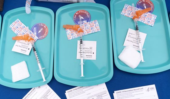 """In this Wednesday, May 19, 2021, photo, Pfizer COVID-19 vaccine doses are prepared for members of the community 12 years and up, at a clinic held by Community of Hope, outside the Washington School for Girls in southeast Washington. The World Health Organization's top vaccines expert says that immunizing children against the coronavirus """"is not a high priority"""" given the extremely limited global supply of doses. During a social media session on Thursday, June 3 Dr. Kate O'Brien said that vaccinating children """"is not a priority from a WHO perspective,"""" even as increasing numbers of rich countries authorize their COVID-19 shots for teenagers and children. (AP Photo/Jacquelyn Martin) **FILE**"""