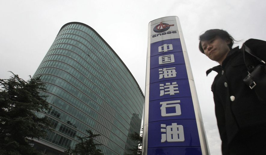 In this Oct. 29, 2008, photo, a woman walks past the headquarters of the state-owned China National Offshore Oil Corp. CNOOC, in Beijing. U.S. President Joe Biden has nearly doubled the list of Chinese companies whose shares are off-limits to U.S. investors in the latest sign he is not softening Washington's stance toward Beijing. Telecoms equipment maker Huawei Technologies, China's big state-owned telecoms companies and China National Offshore Oil Corp. are on the new list of 59 companies. (AP Photo/Ng Han Guan) **FILE**