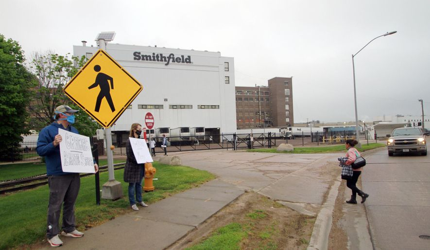 In this May 20, 2020, file photo, residents cheer and hold thank you signs to greet employees of a Smithfield pork processing plant as they begin their shift in Sioux Falls, S.D. Workers at the South Dakota meatpacking plant that became a coronavirus hotspot last year are considering a strike after contract negotiations between Smithfield Foods and the union have stalled, the union said Wednesday, June 2, 2021. (AP Photo/Stephen Groves, File)  **FILE**