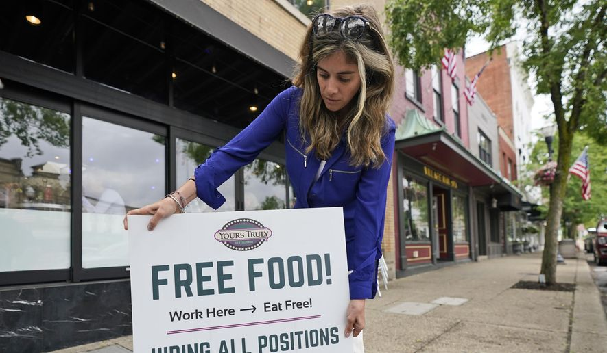Coleen Piteo, director of marketing at Yours Truly restaurant, puts out a sign for hiring, Thursday, June 3, 2021, in Chagrin Falls, Ohio. (AP Photo/Tony Dejak)