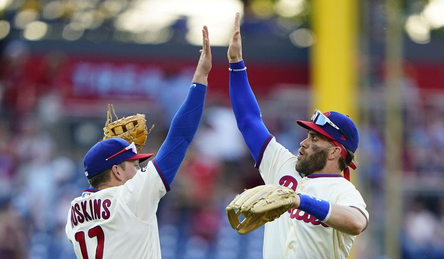 Philadelphia Phillies' Bryce Harper, right, and Rhys Hoskins celebrate after the Phillies won a baseball game against the Washington Nationals, Saturday, June 5, 2021, in Philadelphia. (AP Photo/Matt Slocum)