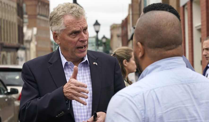 Democratic gubernatorial candidate, former Gov. Terry McAuliffe, left, talks with supporters during a tour of downtown Petersburg, Va., Saturday, May 29, 2021. McAuliffe faces four other Democrats in the a primary June 8. (AP Photo/Steve Helber)