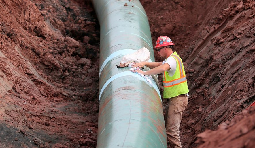 In this Aug. 21, 2017, file photo, a pipe fitter lays the finishing touches to the replacement of Enbridge Energy's Line 3 crude oil pipeline stretch in Superior, Wisc. Environmental and tribal groups opposed to Enbridge Energy's plan to replace its aging Line 3 crude oil pipeline are planning large-scale protests with potential arrests Monday, June 7, 2021, as the Canadian-based company gears up for a final construction push. (Richard Tsong-Taatarii/Star Tribune via AP)