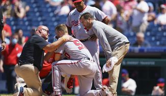 Nationals athletic trainer Paul Lessard, left, tries to stop the bleeding by Austin Voth, center left, with manager Dave Martinez, center right, looking on during the third inning of a baseball game against the Philadelphia Phillies, Sunday, June 6, 2021, in Philadelphia. (AP Photo/Chris Szagola) **FILE**