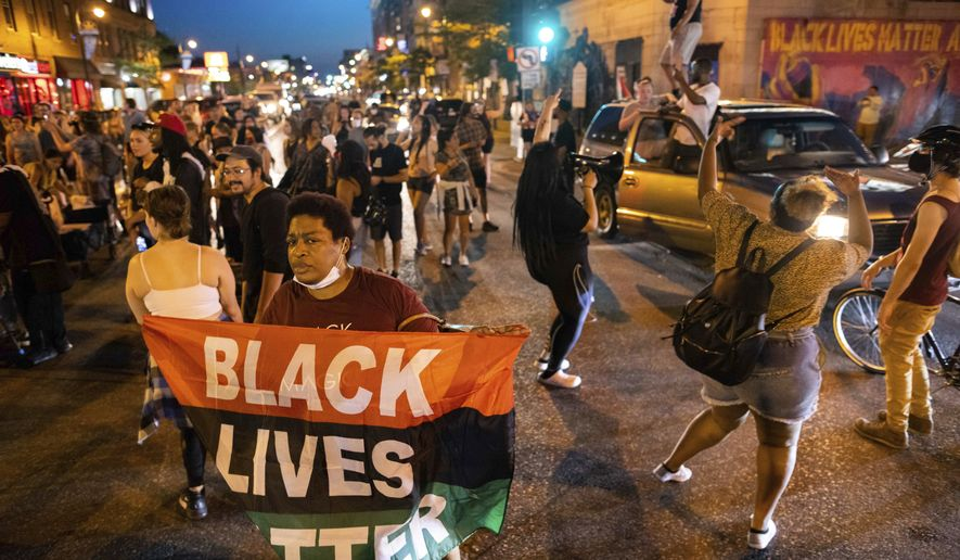 People dance in the streets and hold flags during a march for Winston Boogie Smith Jr. on Saturday, June 5, 2021, in Minneapolis. Smith was fatally shot Thursday by members of a U.S. Marshals task force.. (AP Photo/Christian Monterrosa)