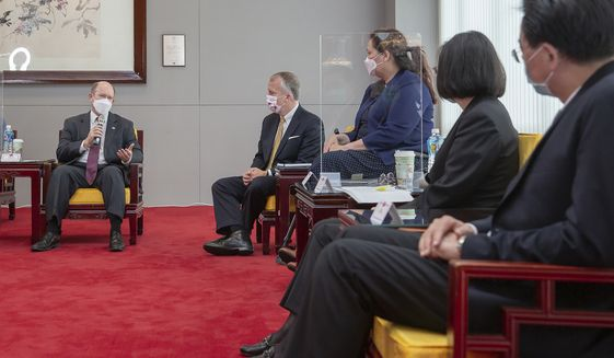 In this photo released by the Taiwan Presidential Office, U.S. Democratic Sen. Christopher Coons of Delaware, left, speaks near Republican Sen. Dan Sullivan of Alaska and Democratic Sen. Tammy Duckworth of Illinois during a meeting with Taiwan President Tsai Ing-wen, second right, in Taipei, Taiwan on Sunday, June 6,2021. The U.S. will give Taiwan 750,000 doses of COVID-19 vaccine, part of President Joe Biden's move to share tens of millions of jabs globally, three American senators said Sunday, after the self-ruled island complained that China is hindering its efforts to secure vaccines as it battles an outbreak. (Taiwan Presidential Office via AP)