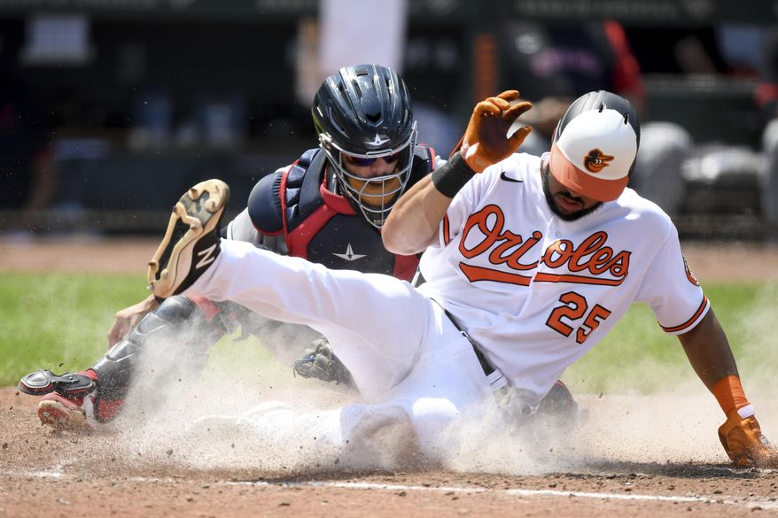 Baltimore Orioles' Anthony Santander, right, slides safely across home plate to score in front of Cleveland Indians catcher Rene Rivera, left, in the fourth inning of a baseball game, Sunday, June 6, 2021, in Baltimore. (AP Photo/Will Newton)