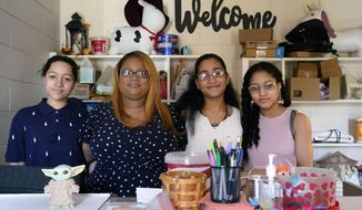 """Aja Purnell-Mitchell, second from left, sits with her three children, Cartier, 14, left; Kyra, 15, and Kyla, 13, at a local food hub in Durham, N.C., on Friday, May 28, 2021, where they often help their mother. """"Getting them back into it, helping them socialize back with their friends, maybe meet some new people, and, of course, pick up the things that they lacked on Zoom,"""" Purnell-Mitchell said, ticking off her hopes for the summer school session ahead, which will be the first time her children have been in the classroom since the coronavirus outbreak took hold in the spring of 2020. (AP Photo/Gerry Broome)"""