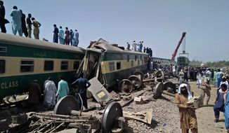 Soldiers and volunteers work at the site of a train collision in Ghotki district in southern Pakistan, Monday, June 7, 2021. Two express trains collided in southern Pakistan early Monday, killing dozens of passengers, authorities said, as rescuers and villagers worked to pull injured people and more bodies from the wreckage. (AP Photo/Waleed Saddique)