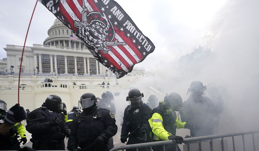 In this Jan. 6, 2021, file photo, U.S. Capitol Police officers hold off rioters loyal to President Donald Trump at the Capitol in Washington. (AP Photo/Julio Cortez, File)