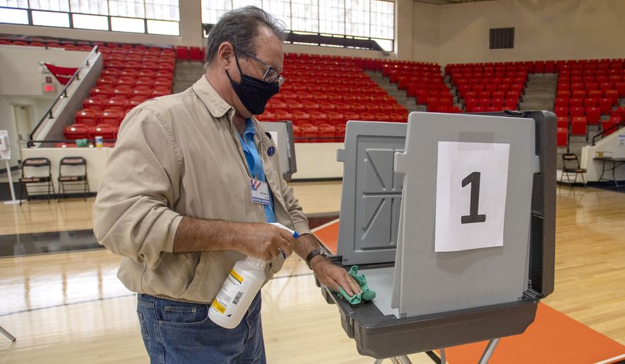Poll worker Phil Dingus cleans one of the voting machines at the Virginia High School precinct during the Virginia Democratic Primary Election, on Tuesday, June 8, 2021, in Bristol, Va. (David Crigger/Bristol Herald Courier via AP) ** FILE **