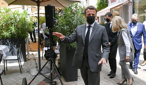 French President Emmanuel Macron arrives for a lunch Tuesday June 8, 2021 in Valence, southeastern France. French President Emmanuel Macron has been slapped in the face by a man during a visit in a small town of southeastern France, Macron's office confirmed. (Philippe Desmazes, Pool via AP)