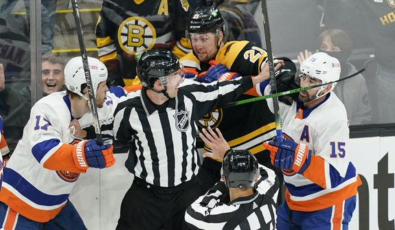 Referees keep Boston Bruins left wing Nick Ritchie (21) from fighting with New York Islanders left wing Matt Martin (17) and right wing Cal Clutterbuck (15) in the first period of Game 1 during an NHL hockey second-round playoff series, Saturday, May 29, 2021, in Boston. (AP Photo/Elise Amendola) **FILE**