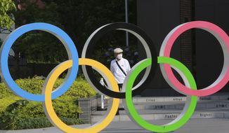A man walks past the Olympic rings in Tokyo, Monday, June 7, 2021. (AP Photo/Koji Sasahara) **FILE**