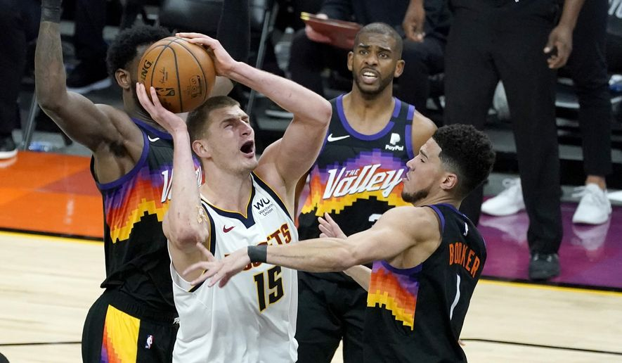 Denver Nuggets center Nikola Jokic (15) shoots over Phoenix Suns guard Devin Booker (1) during Game 1 of an NBA basketball second-round playoff series, Monday, June 7, 2021, in Phoenix. (AP Photo/Matt York) **FILE**