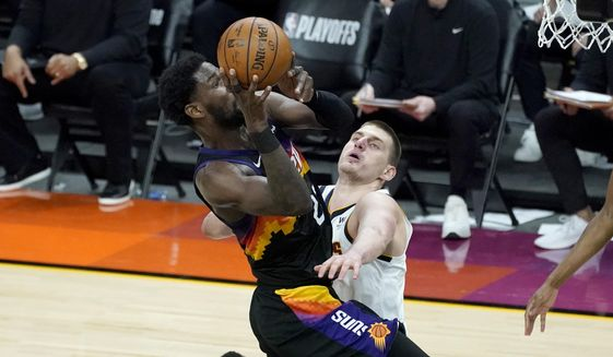 Phoenix Suns center Deandre Ayton is fouled by Denver Nuggets center Nikola Jokic, right, during the second half of Game 1 of an NBA basketball second-round playoff series, Monday, June 7, 2021, in Phoenix. (AP Photo/Matt York) **FILE**