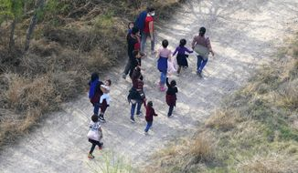 Migrants walk on a dirt road in March, 2021 after crossing the U.S.-Mexico border near Mission, Texas.  (AP Photo/Julio Cortez)