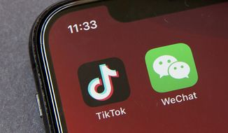 """Icons for the smartphone apps TikTok and WeChat are seen on a smartphone screen in Beijing, in a Friday, Aug. 7, 2020 file photo.  Officials say the White House has dropped Trump-era executive orders that attempted to ban the popular apps TikTok and WeChat and will conduct its own review aimed at identifying national security risks with software applications tied to China. A new executive order directs the Commerce Department to undertake what officials describe as an """"evidence-based"""" analysis of transactions involving apps that are manufactured or supplied or controlled by China. Officials are particularly concerned about apps that collect users' personal data or have connections to Chinese military or intelligence activities. (AP Photo/Mark Schiefelbein, File)  **FILE**"""