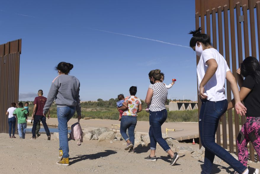 """In this Tuesday, June 8, 2021, photo, a group of Brazilian migrants make their way around a gap in the U.S.-Mexico border in Yuma, Ariz., seeking asylum in the United States after crossing over from Mexico. The Biden administration says it has identified more than 3,900 children separated from their parents at the U.S.-Mexico border under former President Donald Trump's """"zero-tolerance"""" policy on illegal crossings. The Border Patrol's Yuma sector recorded the highest number of separations of the agency's nine sectors on the Mexican border. (AP Photo/Eugene Garcia) **FILE**"""