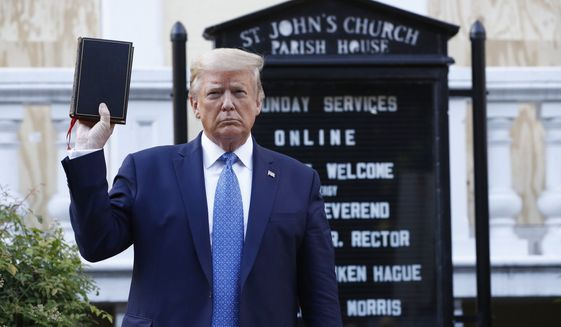 In this June 1, 2020, file photo President Donald Trump holds a Bible as he visits outside St. John's Church across Lafayette Park from the White House in Washington. An internal investigation has determined that the decision to clear racial justice protestors from an area in front of the White House last summer was not influenced by then-President Donald Trumps plans for a photo opportunity at that spot. The report released Wednesday by the Department of Interiors Inspector General concludes that the protestors were cleared by U.S. Park Police on June 1 of last year so new fencing could be installed. (AP Photo/Patrick Semansky) **FILE**