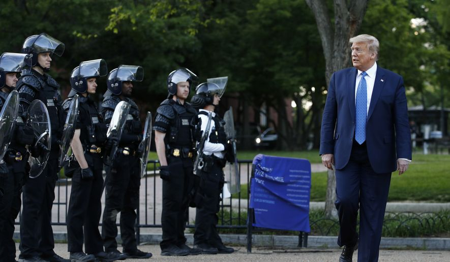 In this June 1, 2020, file photo, President Donald Trump walks past police in Lafayette Park after visiting outside St. John's Church across from the White House in Washington. An internal investigation has determined that the decision to clear racial justice protestors from an area in front of the White House last summer was not influenced by then-President Donald Trump's plans for a photo opportunity at that spot. The report released Wednesday by the Department of Interiors Inspector General concludes that the protestors were cleared by U.S. Park Police on June 1 of last year so new fencing could be installed. (AP Photo/Patrick Semansky/File)