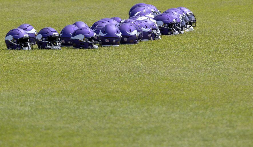 Helmets on the turf during Minnesota Vikings OTAs scrambles Wednesday, June 9, 2021, in Eagan, Minn. (Carlos Gonzalez/Star Tribune via AP)