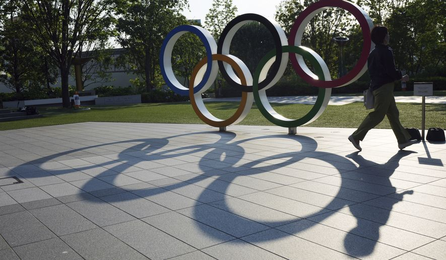 A woman walks by the Olympic Rings near the National Stadium in Tokyo Wednesday, June 9, 2021. Roads were being closed off since last Tuesday around Tokyo Olympic venues, including the new $1.4 billion National Stadium where the opening ceremony is set for July 23.(AP Photo/Eugene Hoshiko)