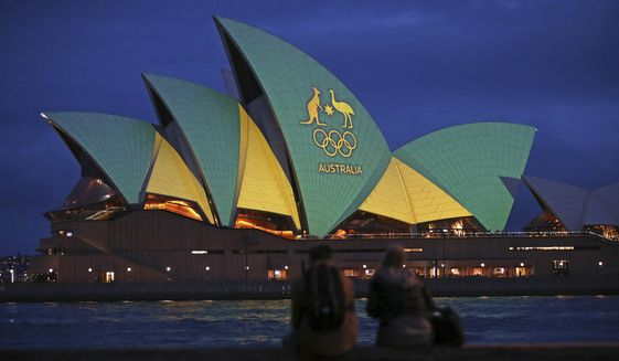 In this Friday, Aug. 5, 2016, file photo, a couple sit on a dock to look at the sails of the Sydney Opera House that are illuminated with the green and gold colors of the Australian Olympic team, as Australia pushes to host the 2032 Olympics.  Brisbane will be offered as the 2032 Olympics host, IOC president Thomas Bach said Thursday June 10, 2021, for International Olympic Committee members to confirm in Tokyo next month. (AP Photo/Rick Rycroft, File) **FILE**