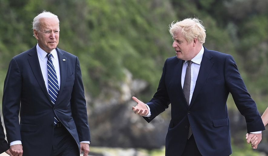 US President Joe Biden, left, talks with Prime Minister Boris Johnson, during a walk, with their wives (not pirctured) outside Carbis Bay Hotel, Carbis Bay, Cornwall, Britain, ahead of the G7 summit, Thursday June 10, 2021. (Toby Melville/Pool Photo via AP)