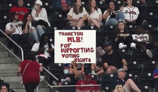 This photo from Monday, April 26, 2021, shows a fan holding a sign supporting Major League Baseball's decision to move the All-Star Game from Atlanta, during a baseball game between the Chicago Cubs and the Atlanta Braves in Atlanta, Georgia. A Manhattan judge has rejected an attempt to force Major League Baseball to return next month's All-Star Game to Atlanta, after it was moved to Denver after Georgia Republicans enacted a restrictive new voting law. (AP Photo/John Bazemore) **FILE**