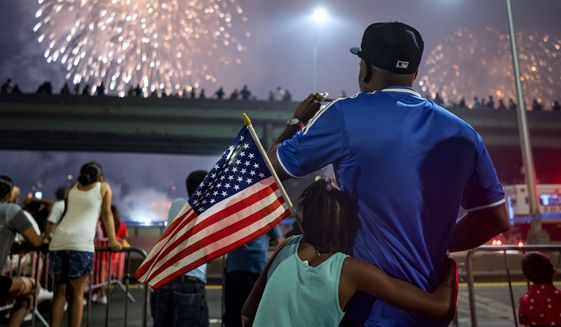 FILE - In this July 4, 2018 file photo, Deon Stewart and his daughter Semiyah, of New York, join other spectators as they watch a fireworks display on the east side of Manhattan, part of Independence Day festivities in New York. The Macy's Fourth of July fireworks show will return to New York City this year. (AP Photo/Craig Ruttle, File)