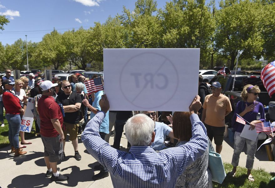 A man holds up a sign against Critical Race Theory during a protest outside a Washoe County School District board meeting on May 25, 2021, in Reno, Nev. Nevada school boards are becoming hotbeds of political polarization where parents are clashing over how to teach students about racism and its role in U.S. history. In Washoe County and Carson City, parents spoke Tuesday, June 8, 2021, against the concept of critical race theory being taught in schools, despite the fact that officials in both districts insist they have no plans to include it in lesson plans. (Andy Barron/Reno Gazette-Journal via AP) **FILE**