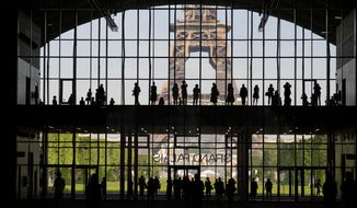 """In this Wednesday, June 9, 2021, file photo, visitors gather during a presentation visit of the """"Grand Palais Ephemere"""", with the Eiffel Tower in the background, in Paris. Europe is opening up to Americans and other visitors after more than a year of COVID-induced restrictions. European governments hope to lure back tourists — and their dollars — back to the continent's trattorias, vistas and cultural treasures. (AP Photo/Francois Mori, File)"""