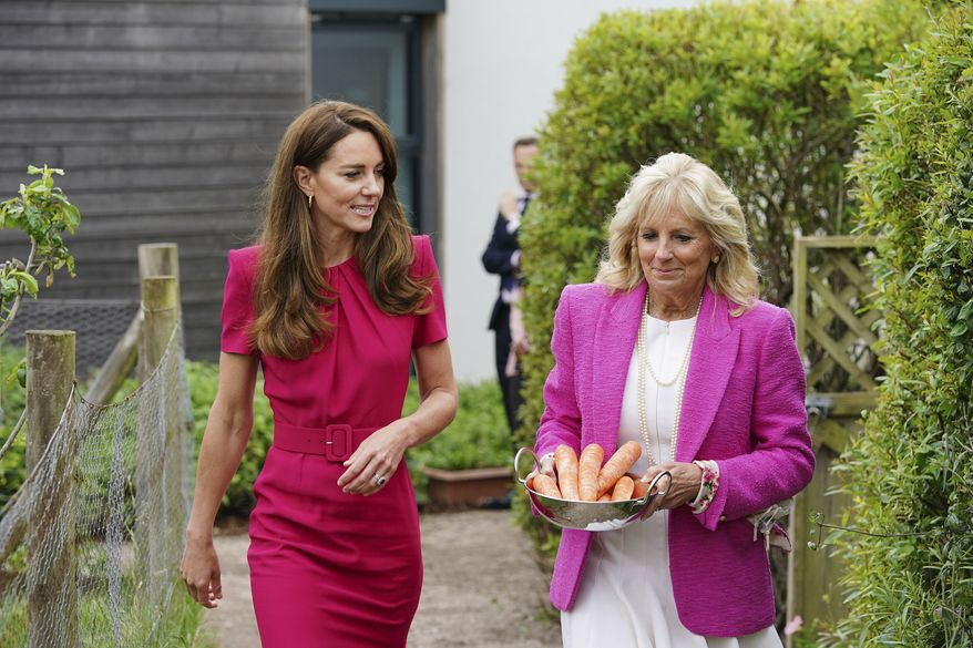 Britain's Kate, Duchess of Cambridge, left, and U.S. first lady Jill Biden, carrying carrots for the school rabbit, Storm, during a visit to Connor Downs Academy in Hayle, West Cornwall, during the G-7 summit in England, Friday, June 11, 2021. (Aaron Chown/Pool photo via AP)