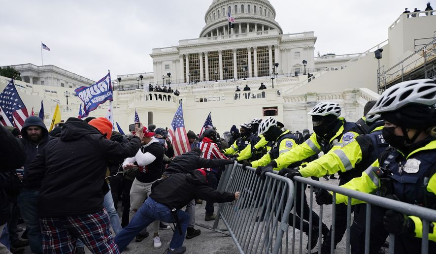 FILE - In this Jan. 6, 2021, file photo, Trump supporters try to break through a police barrier at the Capitol in Washington. A Chicago police officer has been charged with breaching the U.S. Capitol and entering a senator's office during theJan. 6 insurrection.Karol Chwiesiuk, was arrested Friday, June 11 and faces five misdemeanor counts, including entering a restricted building, disrupting government business, and disorderly conduct on Capitol grounds with intent to impede congressional proceeding. (AP Photo/Julio Cortez, File)