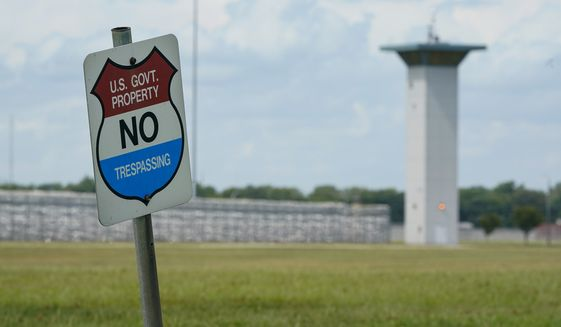 In this Aug. 28, 2020, file photo, a no trespassing sign is displayed outside the federal prison complex in Terre Haute, Ind. Over the past 18 months, 29 prisoners have escaped from federal lockups across the U.S. — and nearly half still have not been caught. (AP Photo/Michael Conroy, File)